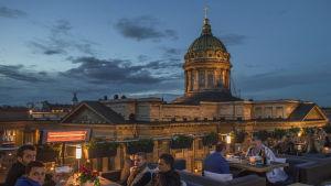 Folk äter middag på en takterass framför Kazankatedralen.