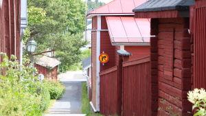 En smal gata som sluttar nedåt. På högra sidan om gatan röda trähus på rad.