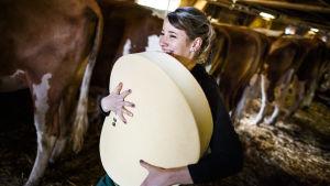 En kvinna bär på en färsk ost i Schweiz under en fest som uppmärksammar slutet på vintern i Alperna.