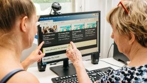 Eläkeikäinen nainen ja häntä digitaidoissa auttava nuorempi sukulainen tietokoneen äärellä, kädet osoittavat koneen näyttöä.