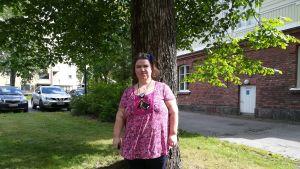 Närvårdare Emma Karlsson står framför ett träd.