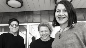Kuunnelman käsikirjoittaja Riina Katajavuori, sen äänisuunnittelija Tiina Luoma ja ohjaaja Elli Salo hymyilevät mustavalkoisessa kuvassa kameralle.