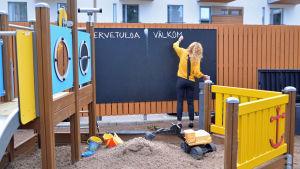 en kvinna står och skriver på en krittavla i en lekpark