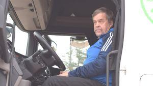 En chaufför i förarhytten på en vit lastbil. Dörren till hytten är öppen.