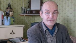 Magnus Gräsbeck i sitt arbetsrum med en spegel och ett skåp i bakgrunden