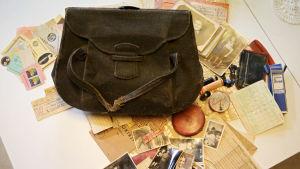 En brun sliten handväska från 1946 med sitt innehåll av fotografier, biljetter och ransoneringskort ligger på ett bord.