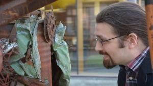 Petter Skult, en man med galsögon, mustasch och skägg, tit