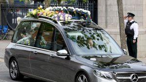 Bil med blommor på taket kör till begravning.