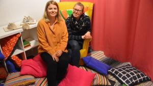 Två kvinnor sitter på en gul fåtölj med en massa färggranna kuddar runtom sig