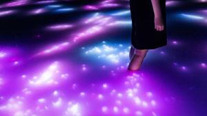 Ihminen seisoo värillisessä vedessä, johon heijastuu kuvia