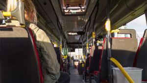 En passagerare sitter inne i en buss. Det finns inte några andra passagerare.