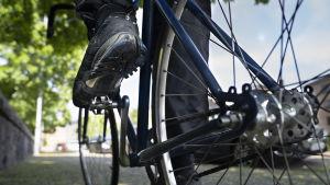 Polkupyöräilijän kenkä ja pyörä lähikuvassa.