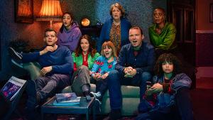 En familj sitter i en soffa med blickarna mot en tv som inte syns i bild. De har alla olika reaktioner av allt från entusiasm till skräck.