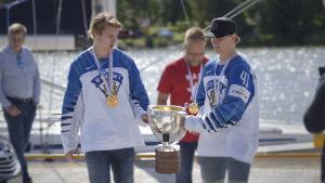 två finska ishockelyspelare bär på vm-pokalen i soligt sommarväder