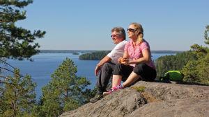 Kaksi ihmistä istuu kalliolla ja katsoo Linnavuorelta Linnansaaren kansallispuiston pääsaarelta aukeaa näkymä ympäröivälle Haukivedelle.