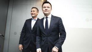 Två leende män i kostym. Pihlajalinnas styrelseordförande Mikko Wirén (till vänster) och Mehiläinens vd Janne-Olli Järvenpää (till höger) på presskonferensen om Mehiläinens bud på Pihlajalinna den 5 november 2019.