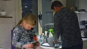 En flicka spelar på telefonen, i bakgrunden diskar en man.