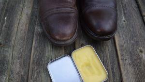 Skor och en burk med smörjmedel framställt av bland annat bivax.
