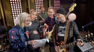 """Musikgruppen """"Lada Egolaeva och Svenska Grammofonstudion"""" står i en ring och tittar i ett notpapper."""
