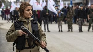 En kvinnlig kurdisk soldat vaktar en begravning i Qamishli
