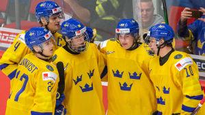 Svenska JVM-spelare firar ett mål tillsammans.