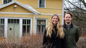 Ida Söderström och Oscar Gräsbäck står utomhus framför ett gult gammalt trähus.