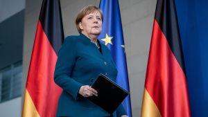 Angela Merkel går på en scen med en mapp i handen. I bakgrunden Tysklands och EU:s flaggor.