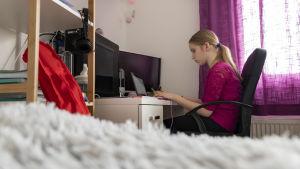 Kuudesluokkalainen Elsa istuu tietokoneellaan ja seuraa oppituntia
