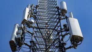 Fyra metalldosor fästa på en 5G-mast.