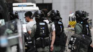 Beväpnade kravallpoliser grep tiotals demokratiaktivister som bröt mot karantänregler och demonstrationsförbud.