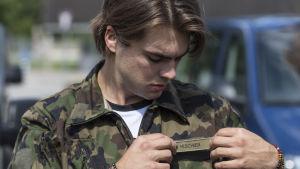Nico Hischier i militärkläder och rättar till sin namnlapp.