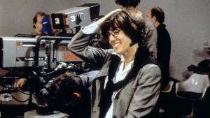 Nora Ephron står vid en filmkamera och ser glad ut.