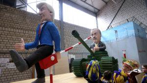 En docka föreställande Donald Trump håller upp en gränsbom för en docka föreställande Turkiets president Recep Erdogan som kör förbi i en stridsvagn.