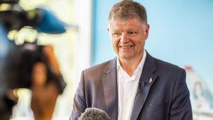 Norwegians koncernchef Jacob Schrem talar i en fluffig mikrofon och ler mot en kamera.