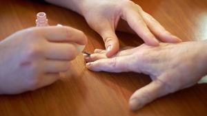 Bild på två par händer. Den med yngre händer lackar naglarna på personen med äldre händer.
