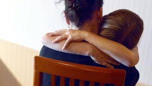 En vuxen person och ett barn kramas på en stol