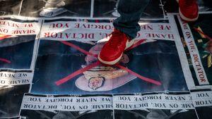 En röd sko trampar på en affisch.