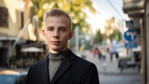 En blond ung man ser in i kameran. Han har på sig en mörkblå rock och en grå polotröja. Han står utomhus på en gata, och bakgrunden är ur fokus.
