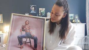 Artisten Kiara Nelson sitter på säng med en bild i ram föreställande hennes första singel. Hon har vita kläder. På bilden sitter hon på en stol.