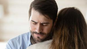 Ledsen man kramar en kvinna.