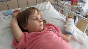 En liten flicka ligger med gipsad arm på sjukhus.