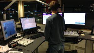 Bild av reporter bakifrån i Yle Åbolands radiostudio.