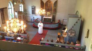 En präst håller gudstjänst i en kyrka.