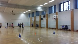 Tyttöjä liikuntatunnilla koulun jumppasalissa.