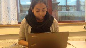 flicka jobbar vid bärbar dator