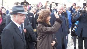 Drottning Silvia vinkar åt folket, kung Carl Gustav i hatt