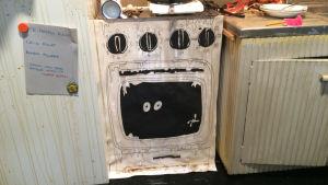 Sotkuinen keittiölavaste, jossa piirretty uuni.