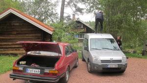 Två bilar står parkerade under en inspelning av Stugor. En fotograf står på den ena bilens tak.