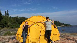 Kasper står vid ett gult geodetiska kupoltält