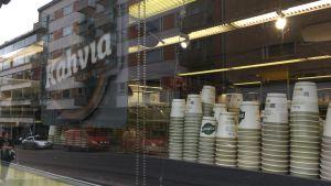 Engångskoppar står uppradade på en hylla. En skylt med texten kaffe hänger bredvid.